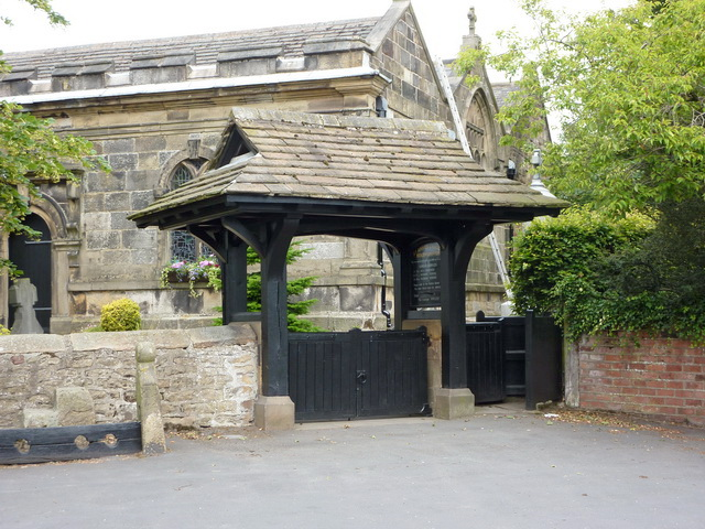Stocks to the left of the lychgate, St Anne's Church in the background