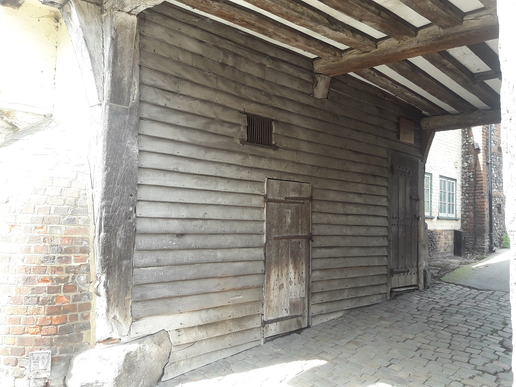 External view of the lock-up - door and grill above in passage known as Church Lane. Second door at the end of the passage leads to a staircase providing access to the first floor of the Church Loft.