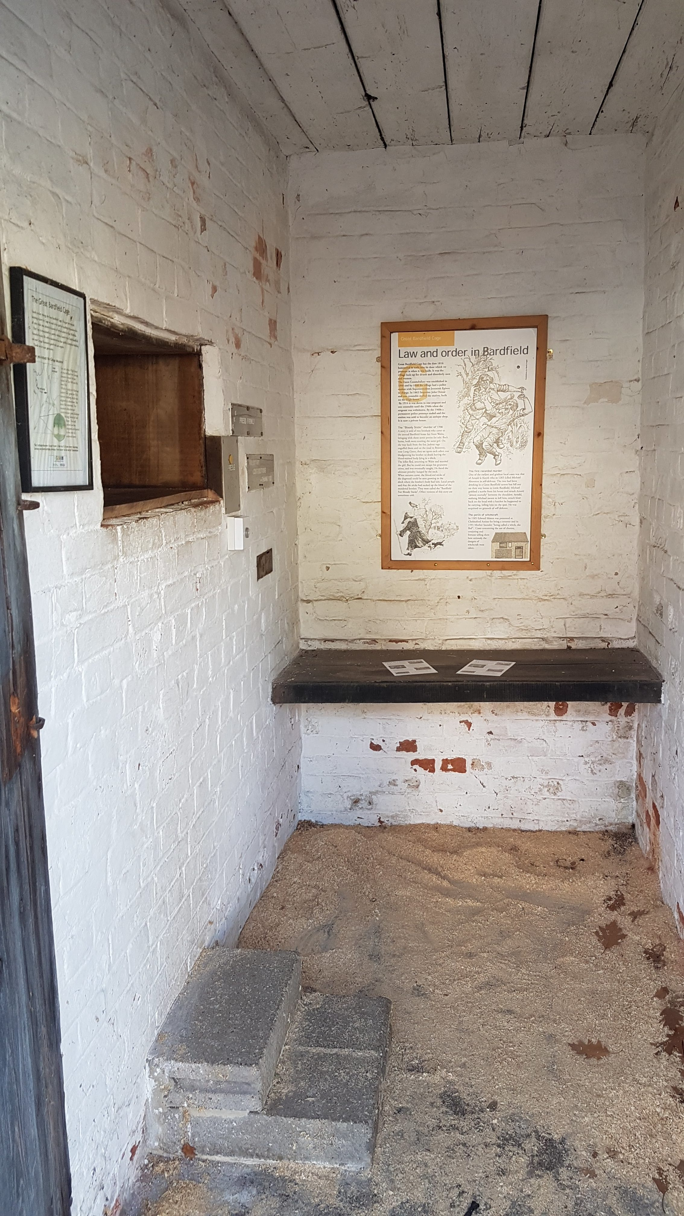 Interior of the first cell. Substantially smaller than the second cell. Wooden bench is probably original, but cut-out on the left-hand wall is almost surely recent to allow visitors to see into the second cell. Information panels, compiled by the Great Bardfield Historical Society, tell the story of the lock-up and crime in the local area in times past.