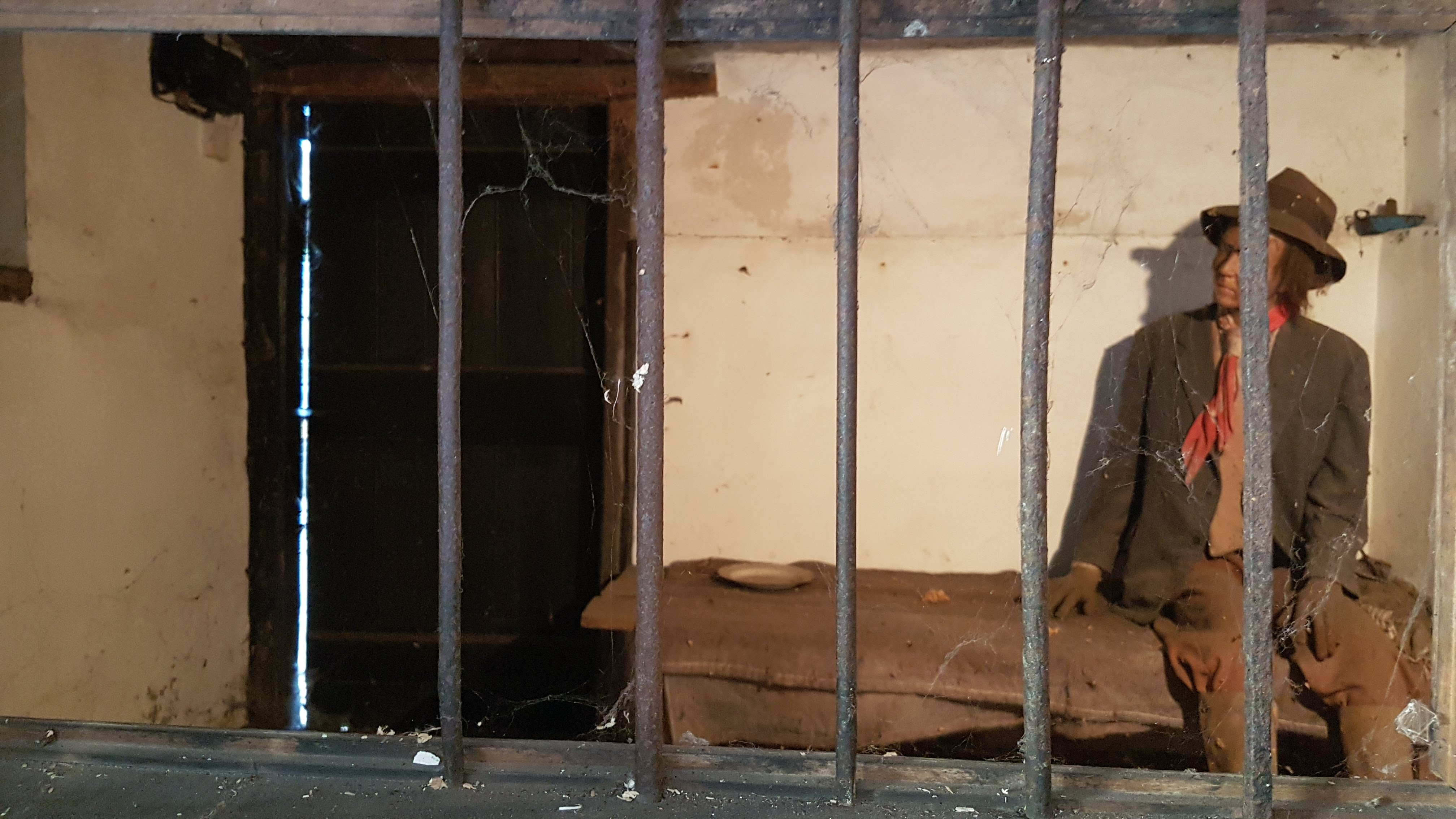 Interior of the second cell, viewed through the cut out. The entrance to the second cell can be seen in the left-hand corner. The corner of the window (seen on the exterior) is also visible on the far left. A mannequin has been placed in the cell to show what it would have looked like with a prisoner inside, together with a wooden bed and a chamber pot.