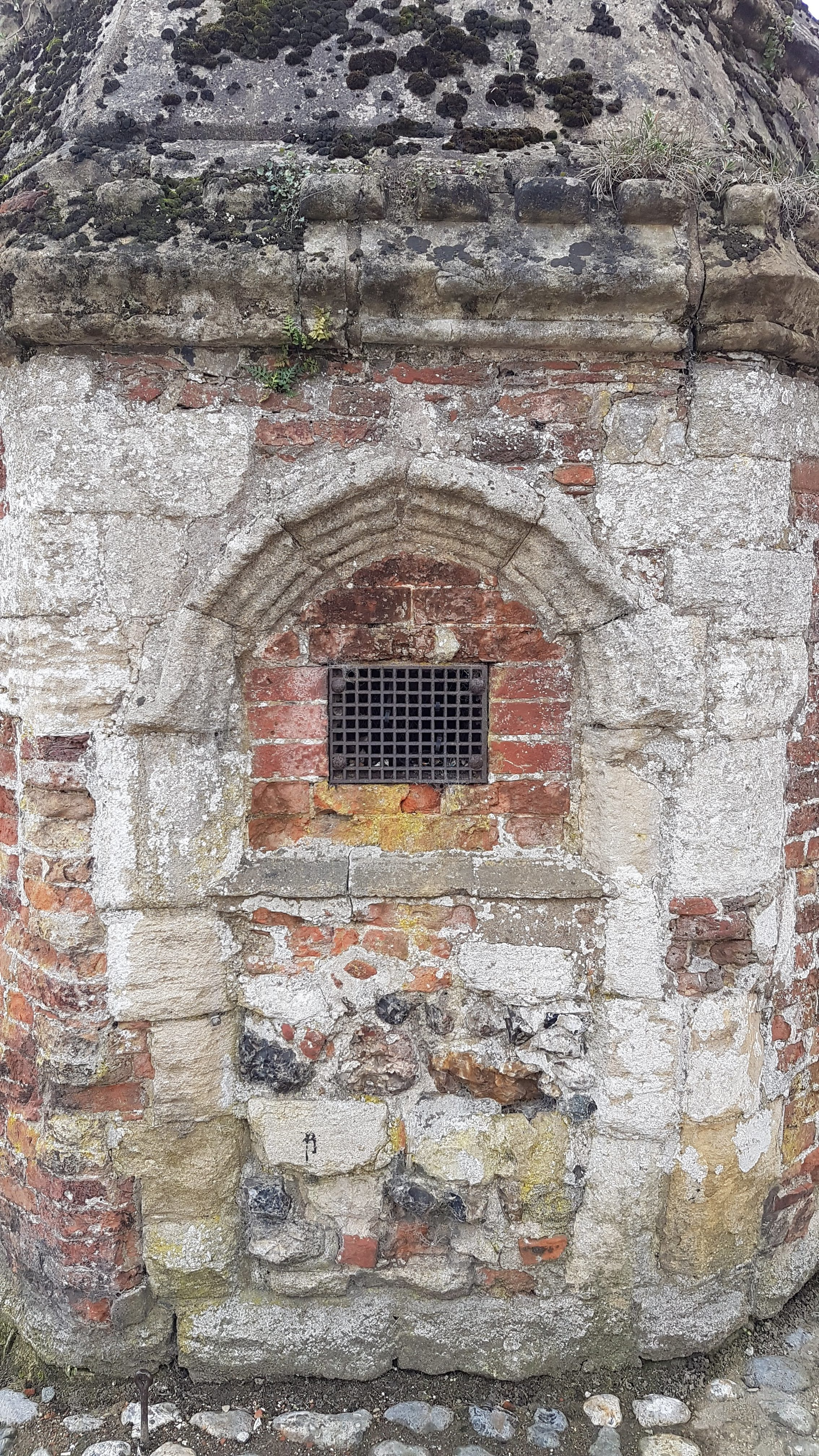 What looks like a small window, or at least an opening for ventilation, covered with an iron grille