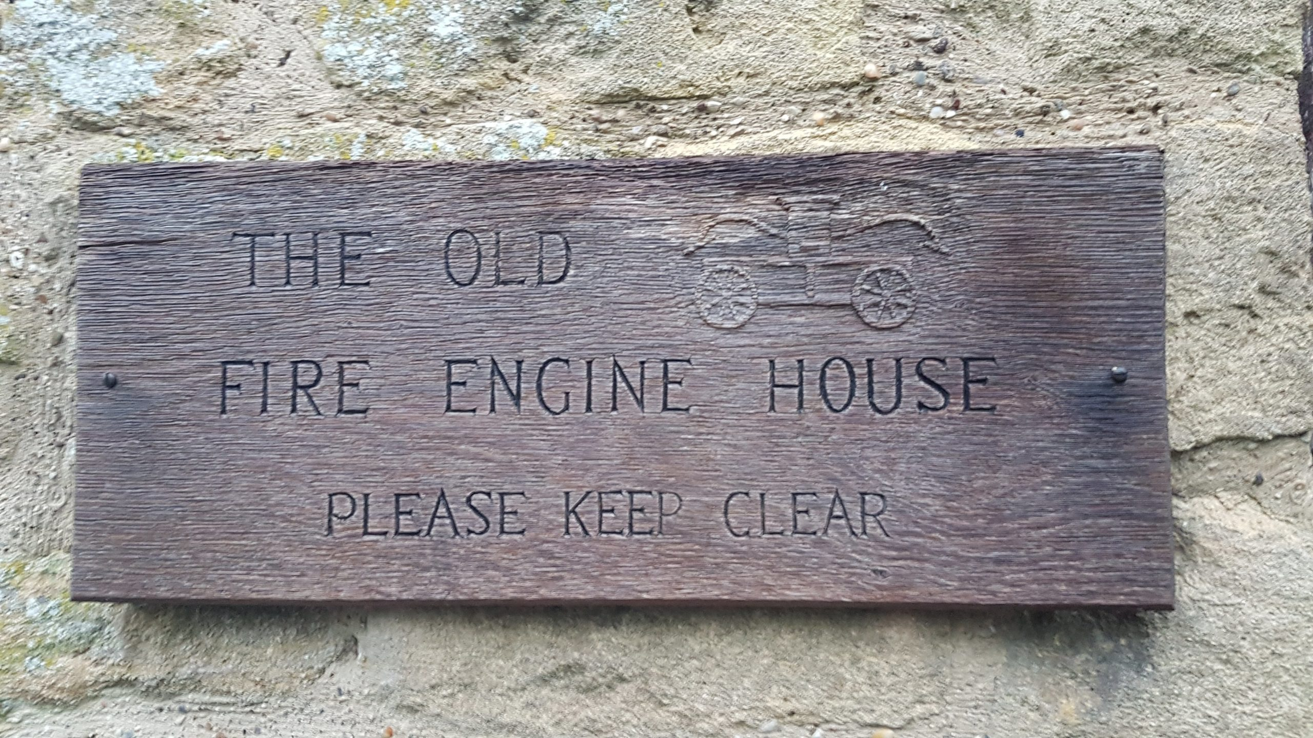 Wooden plaque. Only describes its use as a fire engine house.