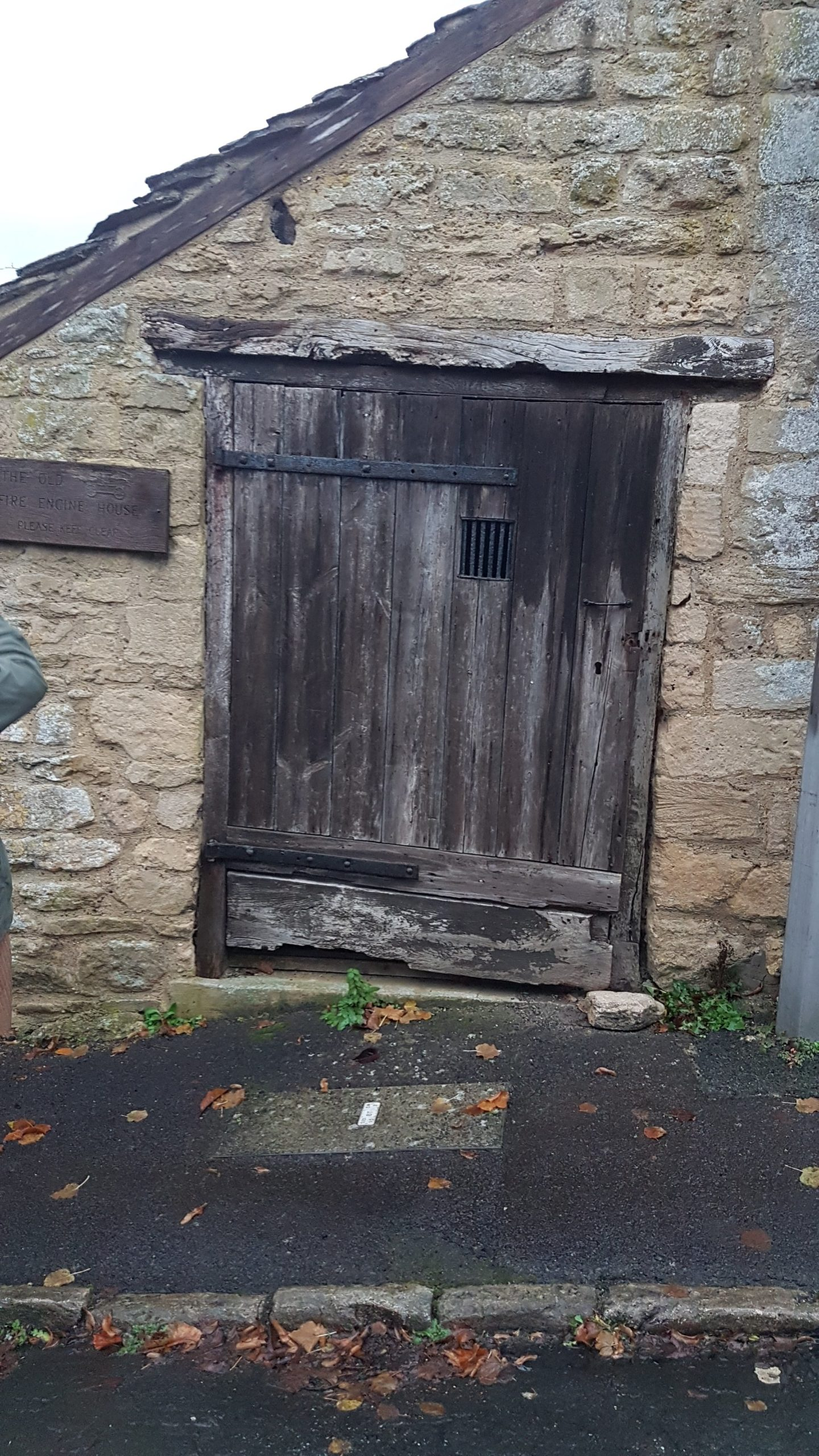 Wooden door, with strap hinges and a window covered with an iron grille
