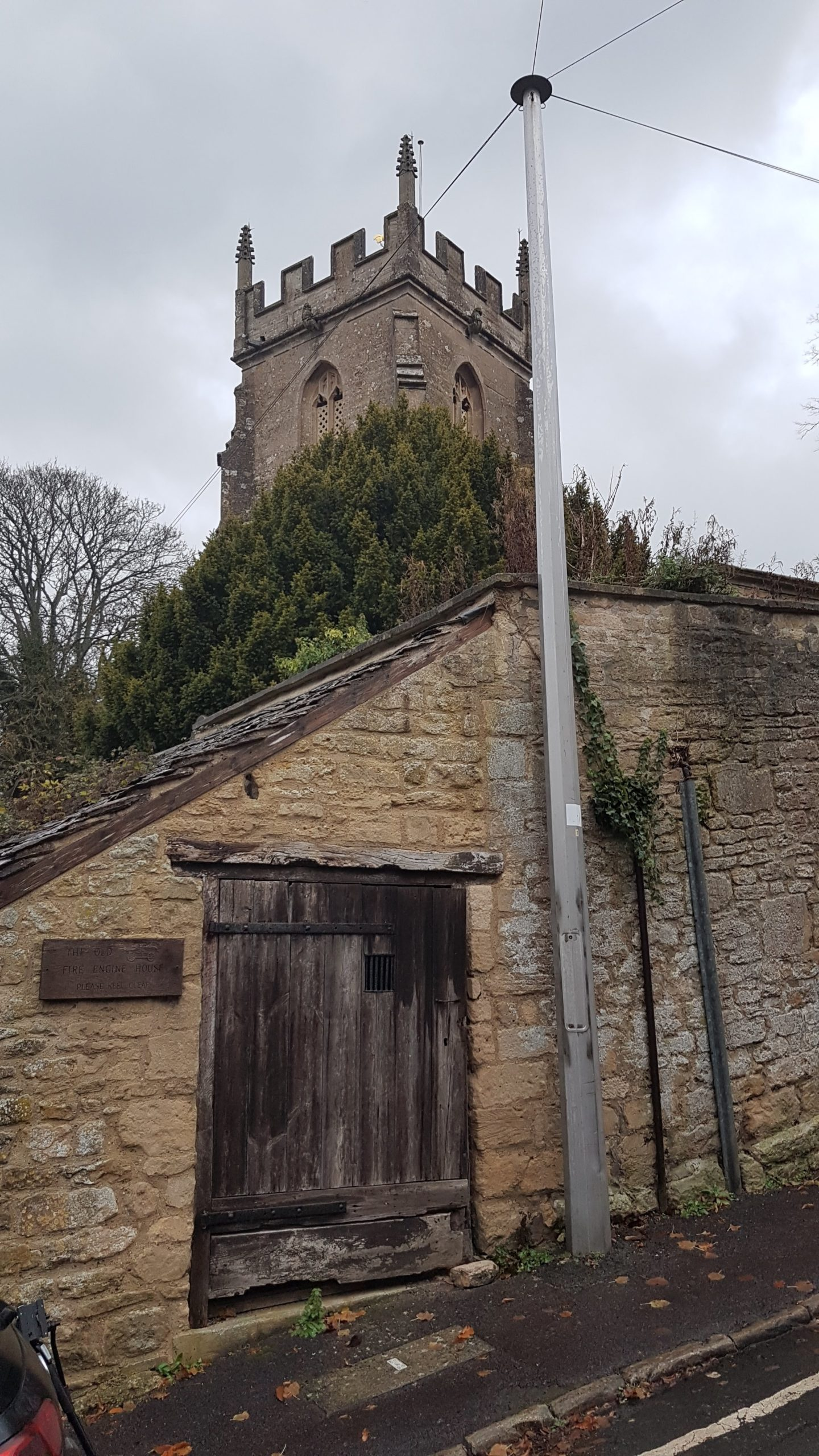 Exterior of the lock-up, showing the parish church in the background.