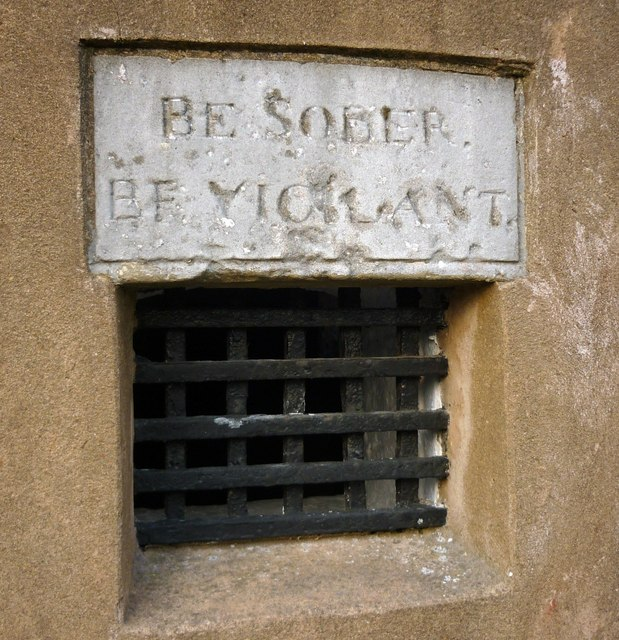 Barred aperture with stone inscription, 'Be Sober, Be Vigilant'