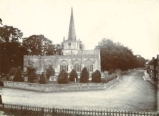 Photograph. St Nicholas's Church with the village road and cottages, Bromham, Wiltshire, late 19th century. Lock-up (blindhouse) can be seen (looking down the road, past the church, on the left-hand side)