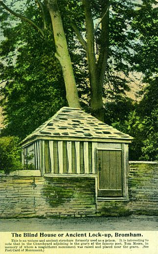 The Blind House or Ancient Lock-up, Bromham. Postcard, view of the blind house, what was once the village lock up, built into the stone wall in front of the churchyard, High Street, Bromham, Wiltshire, 1900-1910. Caption on the front of the postcard reads: