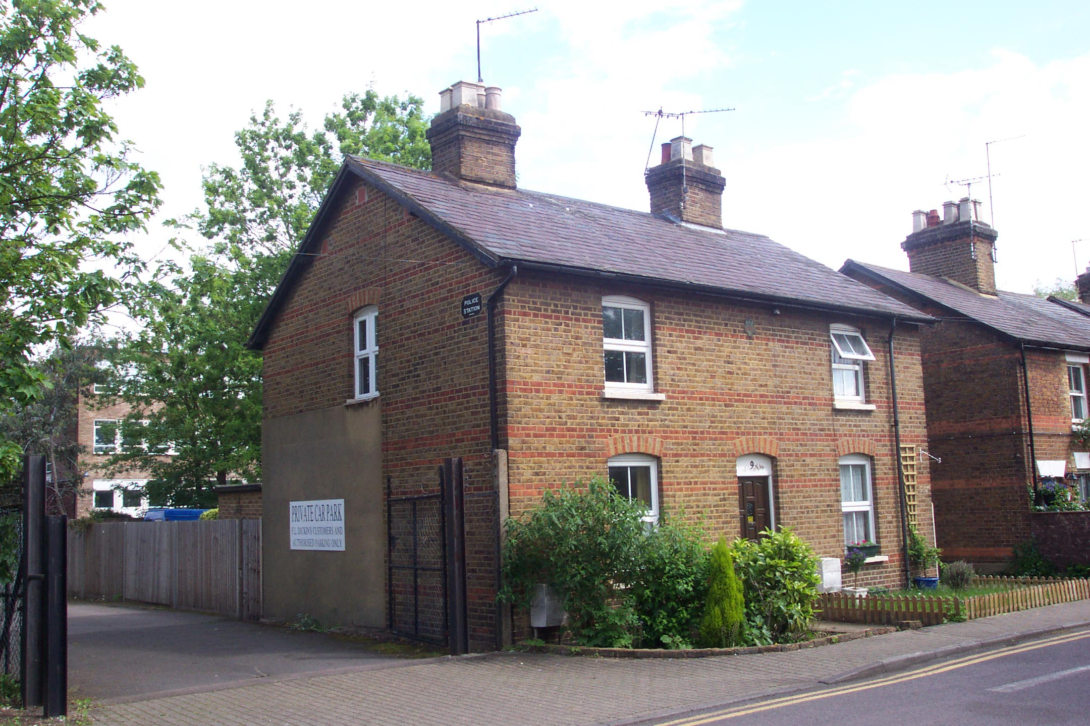 'The Old Police Station' at Rickmansworth: Exterior. Showing the 'shadow' on the side of the building where the external cells were located and attached, as well as the old 'Police Station' sign above and to the right of the cells.