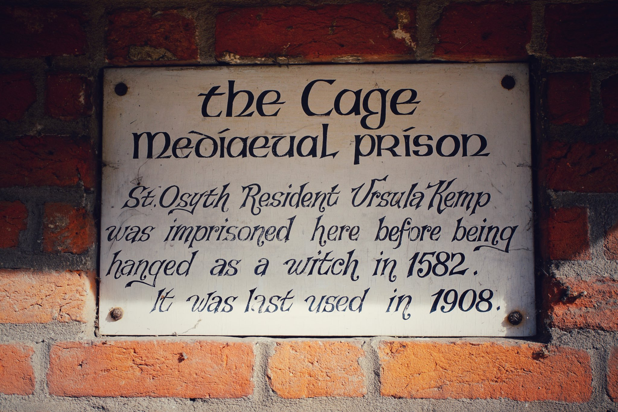 Plaque, on the wall of the old cage