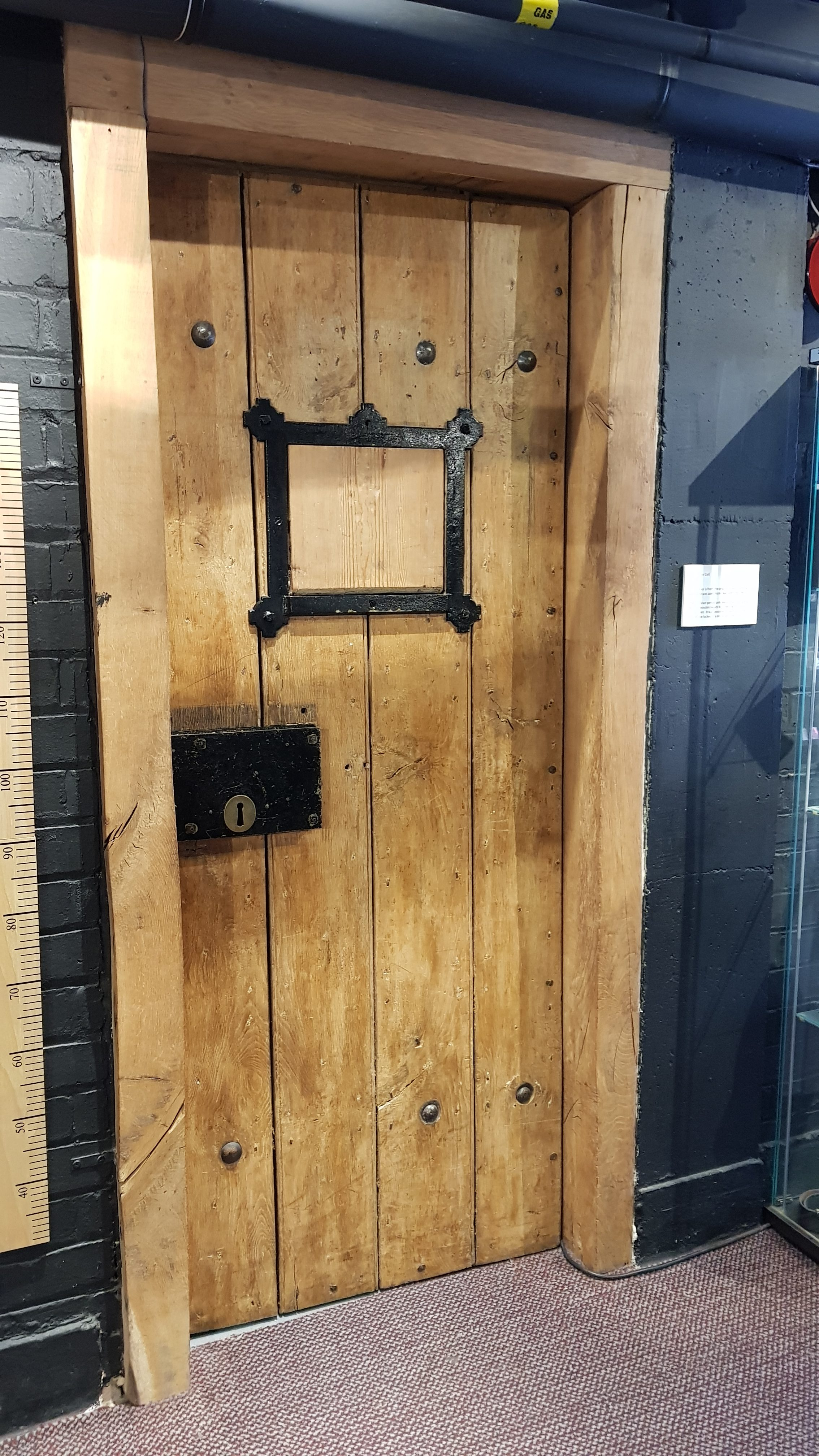 Original cell door from Great Dunmow Police Station, now at Essex Police Museum. Label by the door reads: 'A Victorian Cell. This cell door is from the original Great Dunmow Police Station and was used from 1842 until the 1960s.'