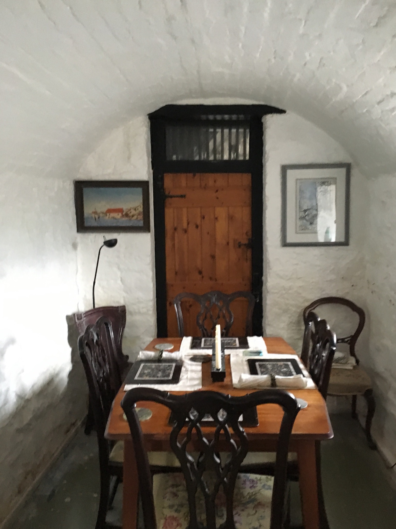 Original cell, now used as a dining room. Notable features include the vaulted ceiling and the cell doorway.