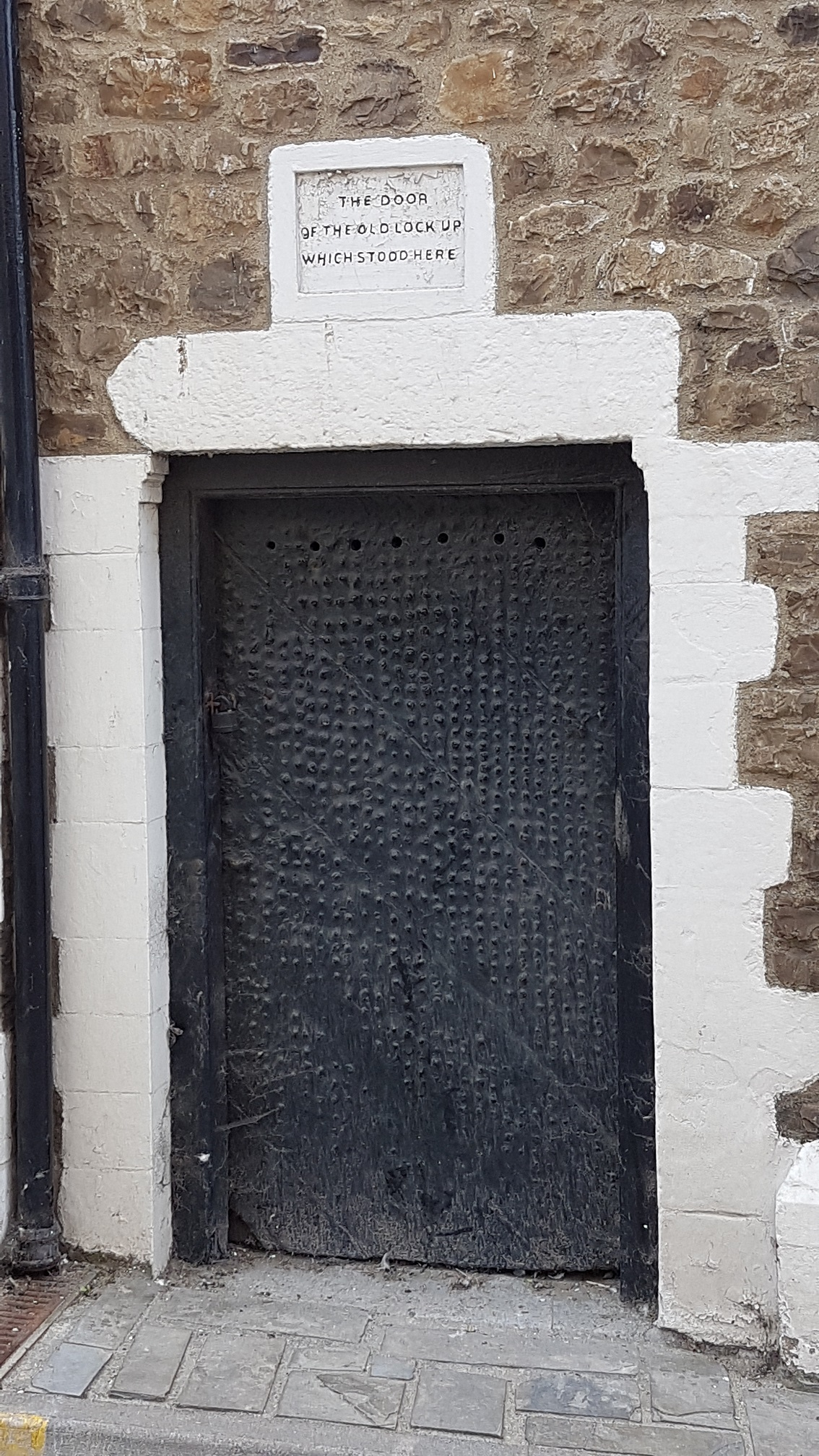 Close-up of door to the lock-up, showing plaque above the lintel, which reads 'The door of the old lock up which stood here'.