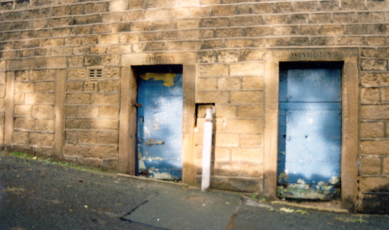 Exterior of the lock-up, showing the three cell doors with the names of local townships inscribed in the lintels above. (c.2003)