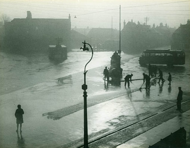 Notes attached to photograph: 'A group of firemen using their hoses and brushes, appearing to be cleaning a set of hoses lined up on the ground next to the town pump in Market Place, with a bus parked on the right and the lockup cum weighbridge on the left, and houses beyond, includes onlookers and a street light in the foreground, Melksham, Wiltshire 1939-1946.'