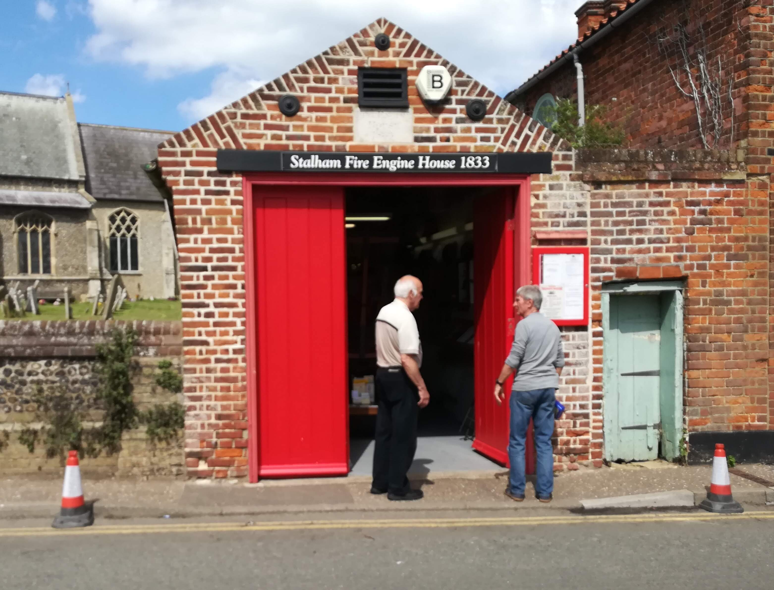 Exterior, showing fire engine house with open doors (lock-up to right with green door)