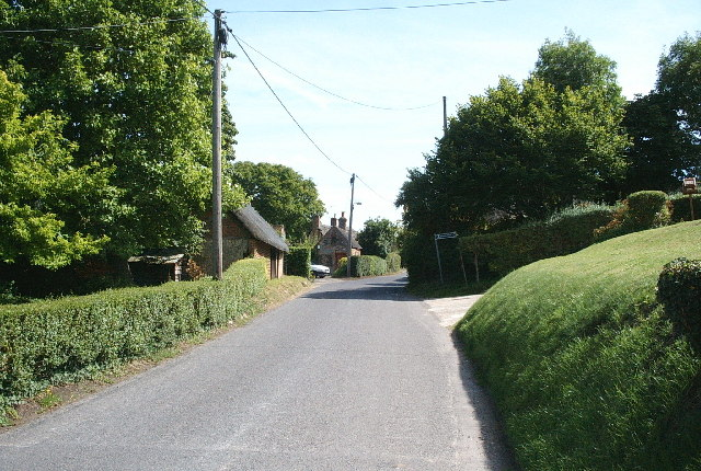 View out of the village, southeast, showing old Village Lock-up centre frame and southern footpath approach to Bedwyn Brail on the right.