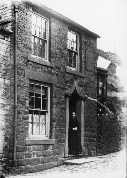 Exterior of the Drunkards Cottage in c.1899, showing Thomas Handford's widow standing in the doorway.