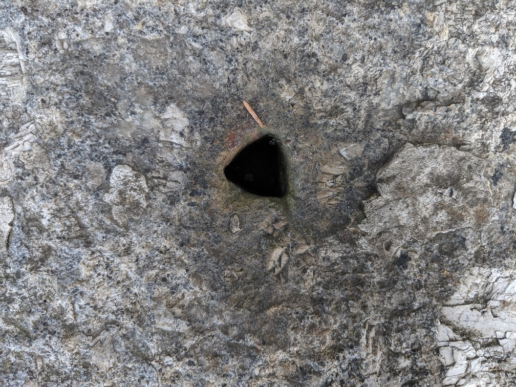 Close-up of the hole in the window sil. It is triangular in shape - not because the cell-window bars were triangular, but because the shape was easier to cut into the stone.